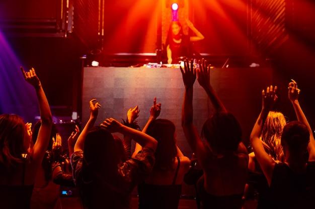 Silhouet afbeelding van mensen dansen in disco nachtclub op muziek van dj op het podium