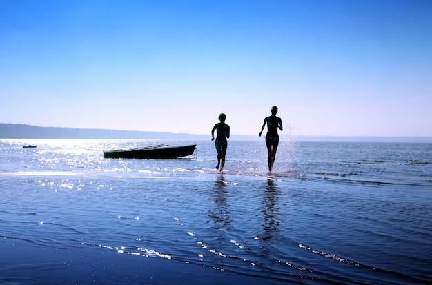 Silhouet afbeelding van twee lopende meisjes in water Premium Foto