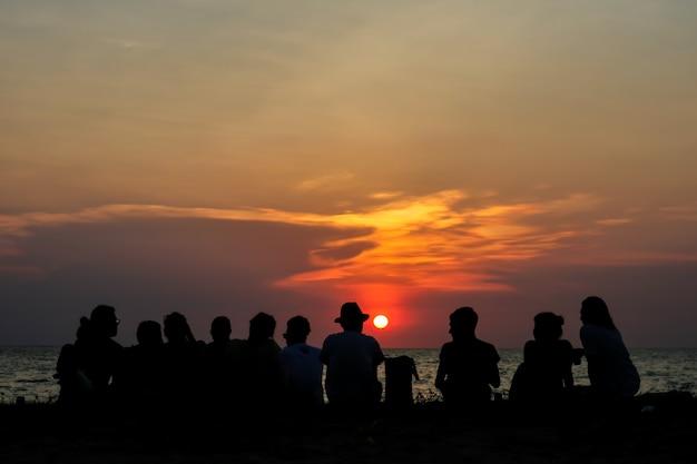 Silhouet alle mensen in familievergadering kijk zonsonderganghemel op strand