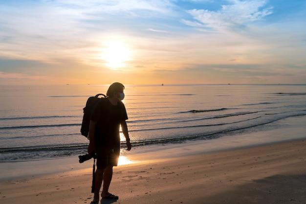 Silhouet aziatische man backpacker met beschermend gezichtsmasker houdt camera vast die op het strand loopt met een warme ochtendzonsopgang in huahin, thailand