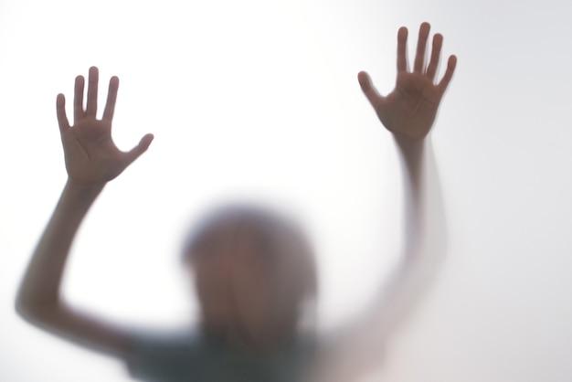 Silhouet bang jongen staan achter glazen deur. jong geitje dat twee handen toont. achtergrond die gevaarlijk, angst, hulp, rondspoken, horror en paniek vertegenwoordigt. tienerproblemen, negatief emotiesconcept.