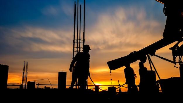 Silhouet bouwvakker beton gieten tijdens commerciële betonnen vloeren van gebouw in bouwplaats
