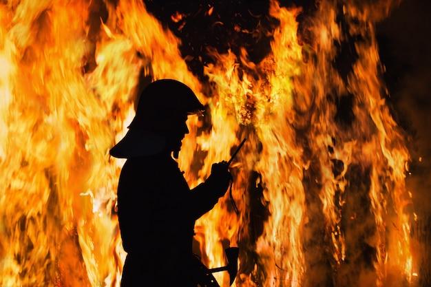 Silhouet brandweerman in brand in de nacht