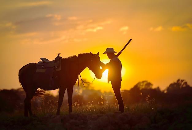 Silhouet cowboy die een paard berijdt op sunset ang thong in thailand.