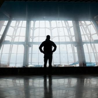 Silhouet dat van de mens zich over venster bevindt