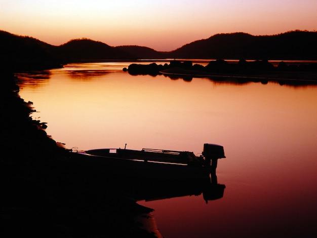 Silhouet dat van een motorboot op het lichaam van een meer is ontsproten dat door bergen tijdens zonsondergang wordt omringd