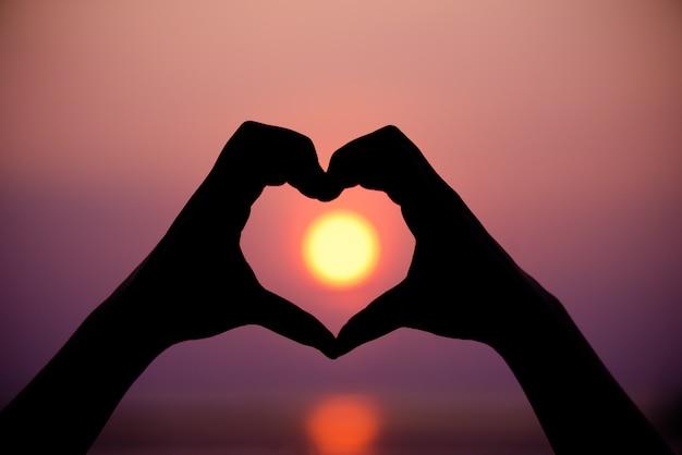 Silhouet de vrouwenhanden om hartvorm op zonsondergangachtergrond te zijn.