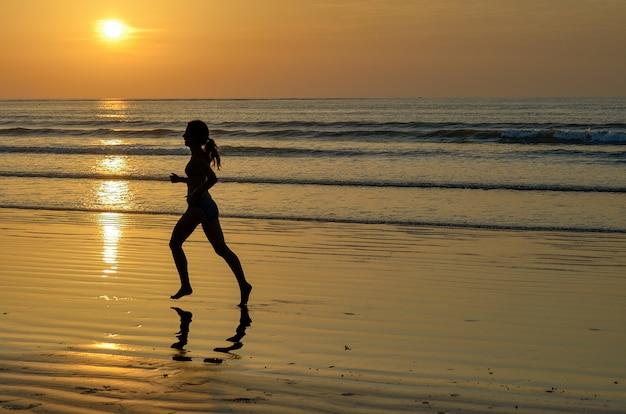 Silhouet die van vrouw jogger op zonsondergangstrand, geschiktheid en gezond het levensconcept lopen