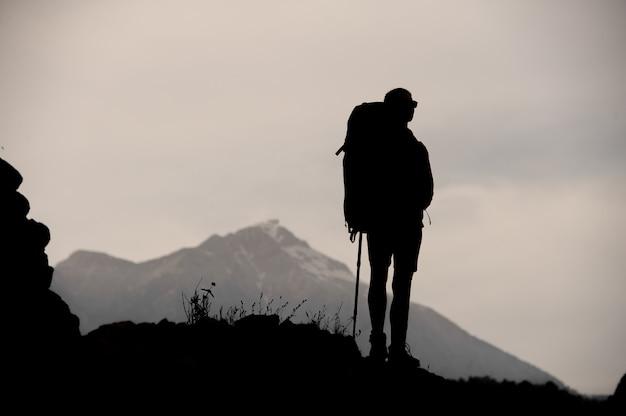 Silhouet die van vrouwelijke wandelaar zich bovenop berg bevinden