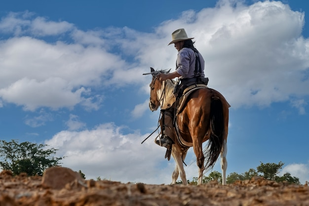 Silhouet en vervaging van actie cowboy met een pistool te paard.