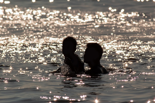 Silhouet gelukkige vader en zoon spelen in water