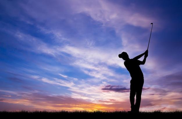 Silhouet golfer golfen tijdens prachtige zonsondergang