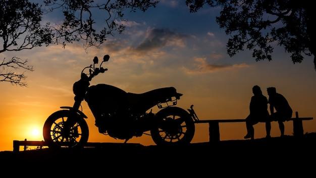 Silhouet grote fiets motorfiets met paar samen zitten op de berg bij zonsondergang