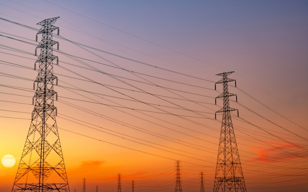 Silhouet hoogspanning elektrische pyloon en elektrische draad met paarse en rode avondrood. elektriciteitspalen bij zonsondergang.
