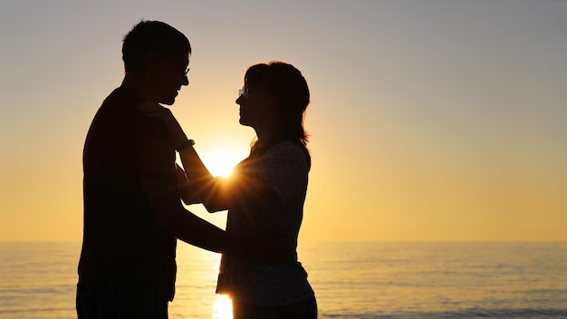 Silhouet, jonge man en vrouw zijn verliefd, kijken elkaar aan