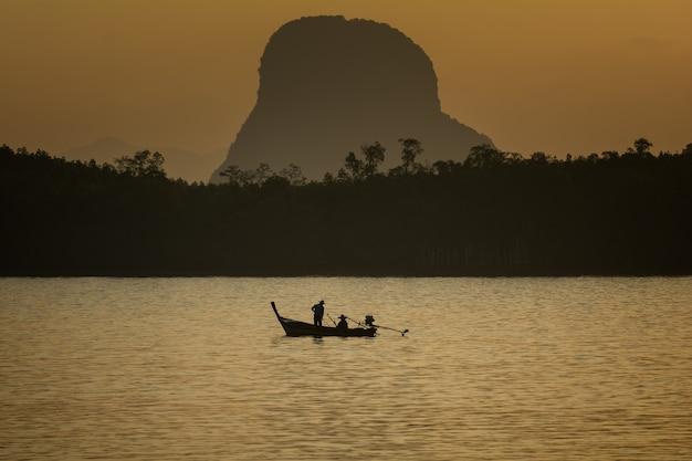 Silhouet levensstijl visser op boot vissen in ochtend gouden licht.
