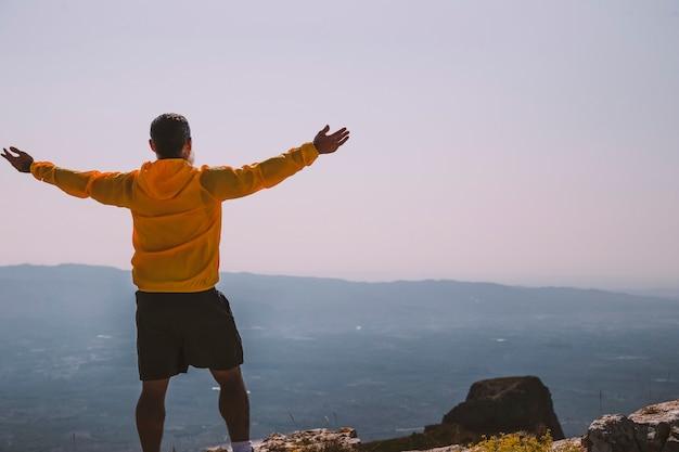 Silhouet man die 's ochtends handen op de berg steekt met vintage licht