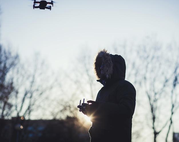 Silhouet man gebruikt drones buiten met zonsondergang