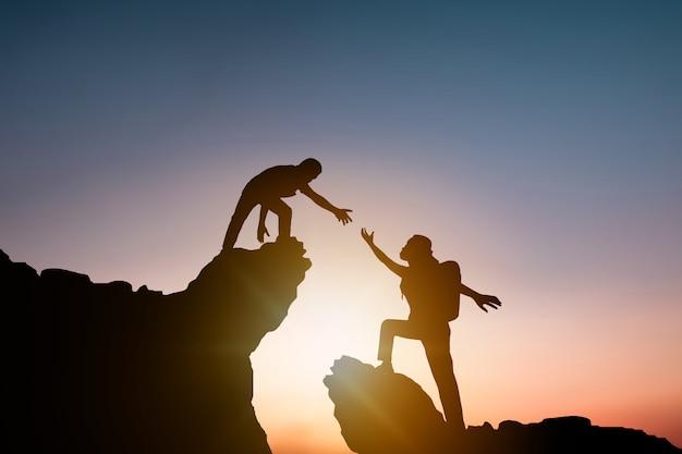 Silhouet mensen helpen andere wandelaar rots en berg te beklimmen