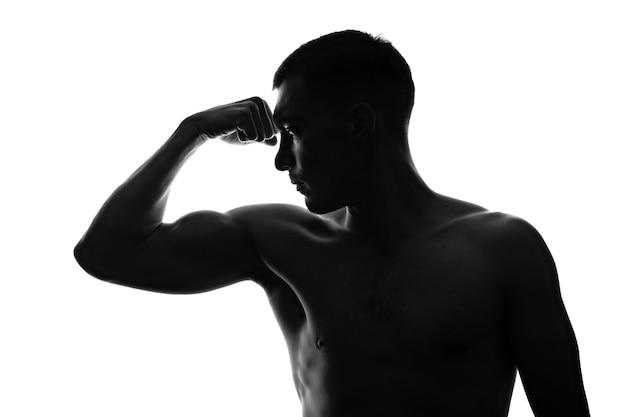 Silhouet portret van gespierde man in profiel toont gespannen biceps op zijn arm met blote torso