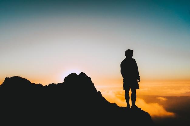 Silhouet shot van een man die op een klif staat en naar de zonsondergang kijkt