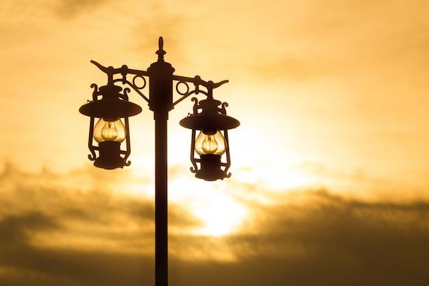 Silhouet smeedijzeren straatlantaarn bij zonsondergang