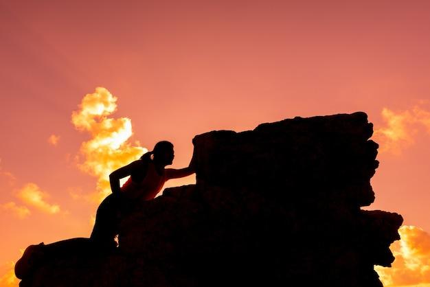 Silhouet sportieve vrouw klimmen op de klif. succes en doelconcept. sterk en gezond voor buitenactiviteiten.