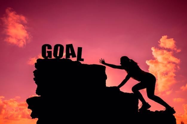 Silhouet sportieve vrouw klimmen op de klif. zakelijk succes en doel concept.