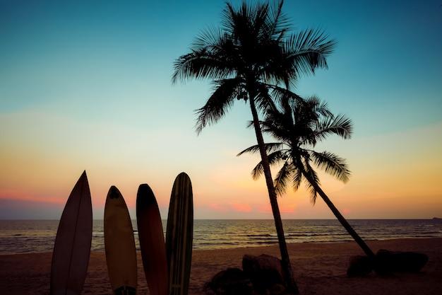 Silhouet surfplank op strand bij zonsondergang in de zomer