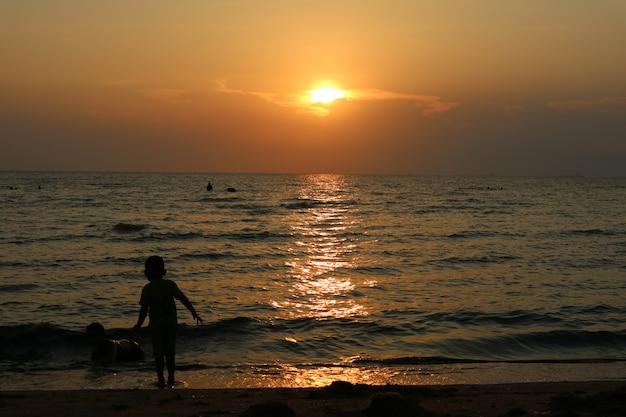 Silhouet twee jong geitjespel op overzeese zonsondergang, één jong geitjetribune op strand