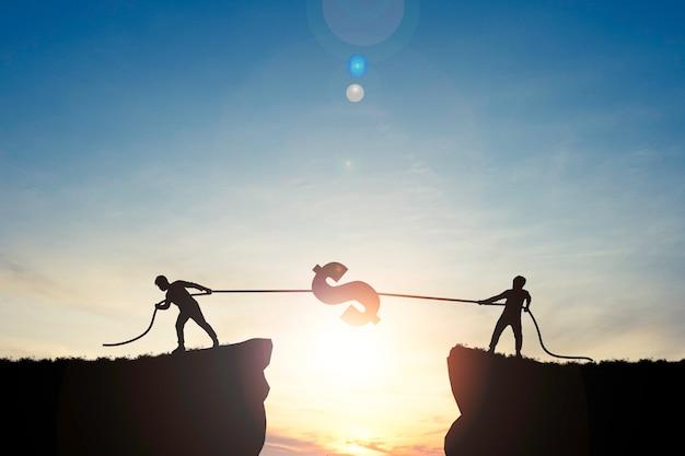 Silhouet twee mannen dollarteken trekken op heuvel met blauwe hemel op zonsopgang.