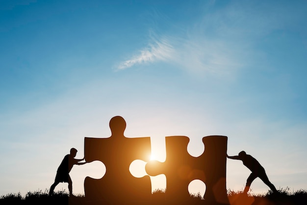 Silhouet twee mannen duwen om puzzel te verbinden met zonlicht en blauwe lucht.