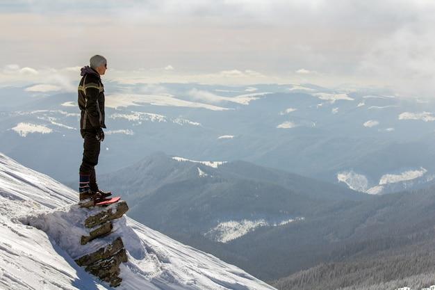 Silhouet van alleen toerist die zich op sneeuwbergbovenkant bevindt die van mening en voltooiing op heldere zonnige de winterdag geniet. avontuur, buitenactiviteiten en een gezond levensstijlconcept.