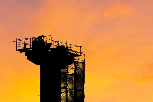 Silhouet van arbeidersteam op bouwplaats, infrastructuurbouwplaats bij zonsondergang in de avondtijd