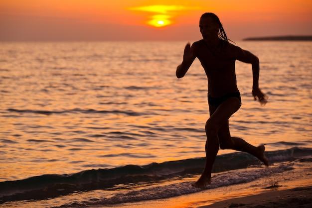 Silhouet van atletische jongeman loopt op de rand van het zeewater tijdens kleurrijke gouden zonsondergang op zomerdag. vakanties, reizen, actief gezond levensstijlconcept