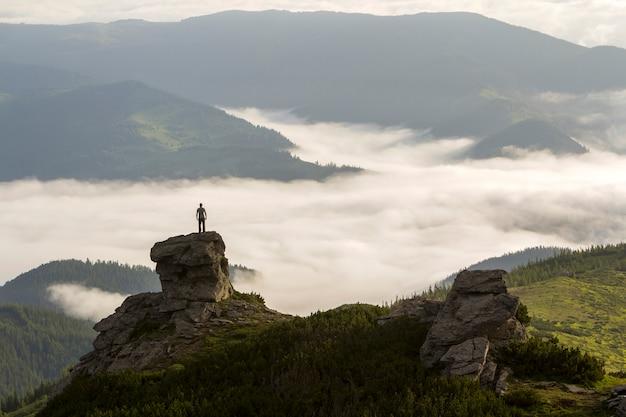 Silhouet van atletische klimmer toerist op hoge rotsachtige formatie op bergdal gevuld met witte gezwollen wolken en mist en bedekt met groenblijvende bos berghellingen