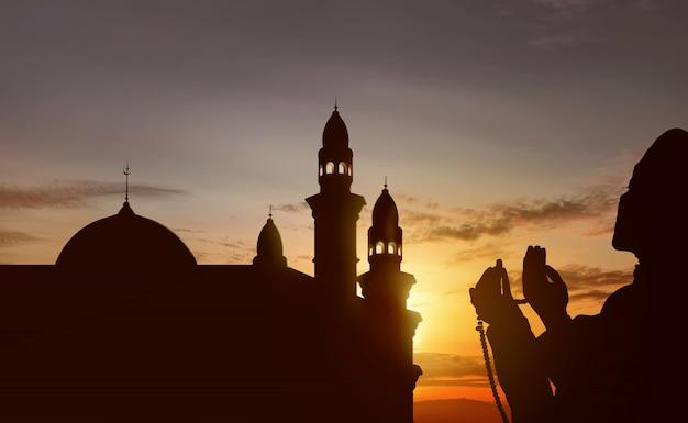 Silhouet van aziatische moslim die met gebedparels bidt