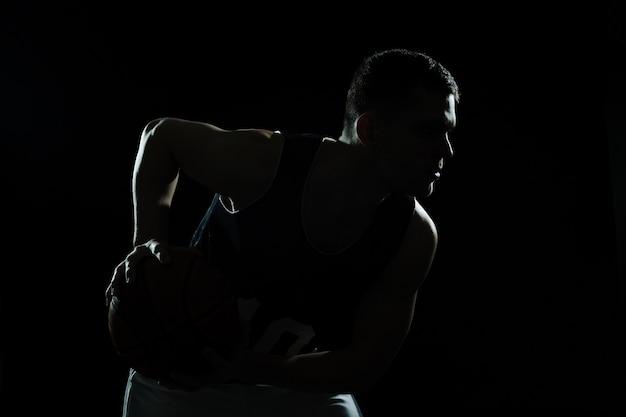 Silhouet van basketbal speler die de bal op zwarte achtergrond