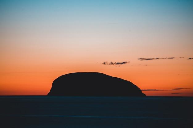 Silhouet van berg dichtbij watermassa