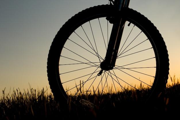 Silhouet van bergfiets op de zonsondergangachtergrond.