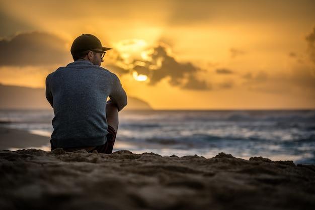 Silhouet van blanke man zittend op sunset beach in hawaii kijkt uit op de zonsondergang over de oceaan