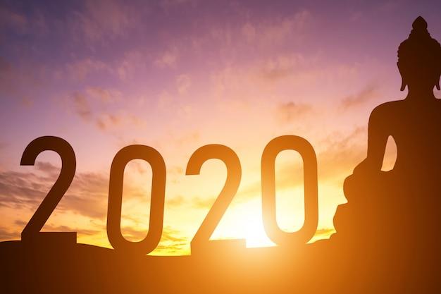 Silhouet van boeddhabeeld bij zonsopgang met 2020