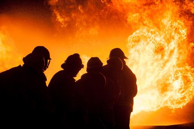 Silhouet van brandweerlieden die een woedend vuur bestrijden met enorme vlammen van brandend hout