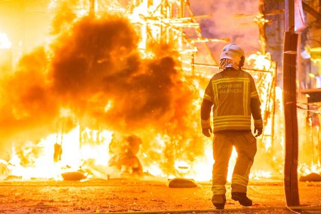 Silhouet van brandweerman die een brand in een straat tijdens een nacht probeert te controleren.