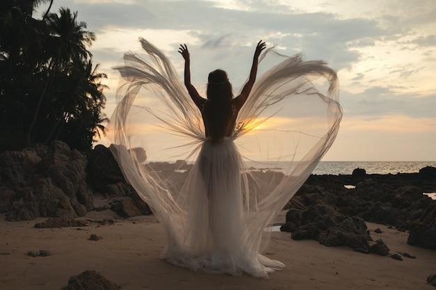 Silhouet van bruid die mooie huwelijkskleding op het strand draagt