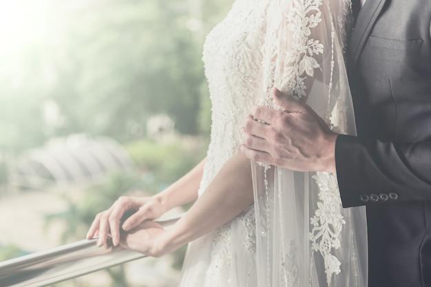Silhouet van bruid en bruidegom houden een boeket van witte bloemen in de buurt van het venster. vintage toonkleur