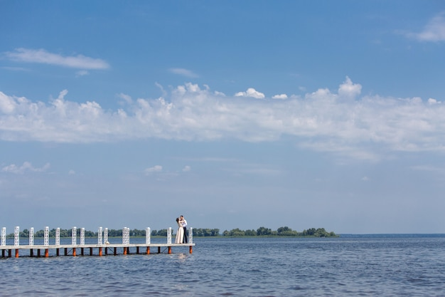Silhouet van bruid en bruidegom lopen op de brug in zonnige dag. trouwdag. man en vrouw knuffelen en zoenen buitenshuis. portret van gelukkige cople verliefd op de natuur