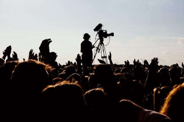 Silhouet van cameraman-operator die een live rockconcert fotografeert