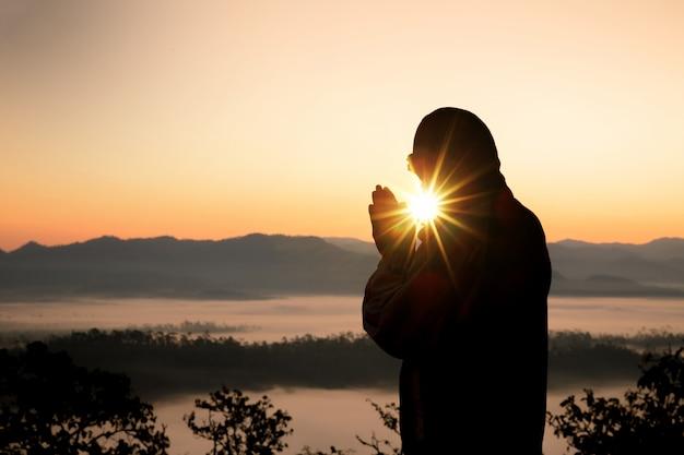 Silhouet van christelijke man hand bidden, spiritualiteit en religie, man bidden tot god.