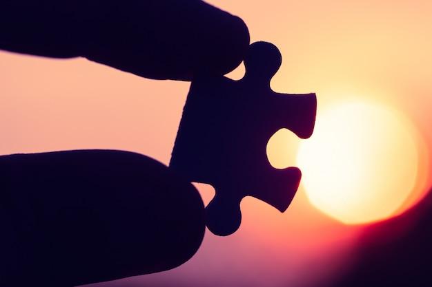 Silhouet van close-uphand die de puzzel houden tegen de avondzon